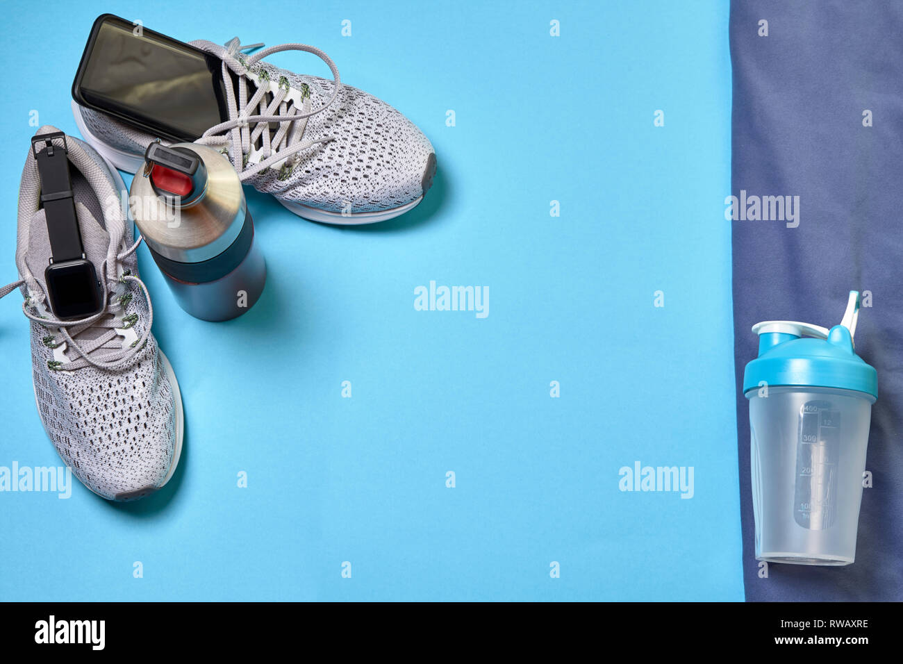 Running shoes with technological accessories and next to a boat of water on a blue background - Stock Image
