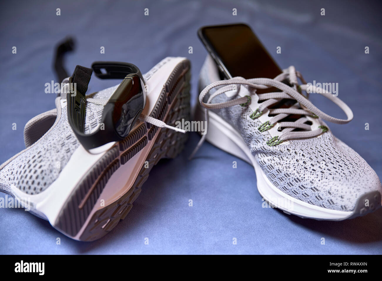 running shoes with technological accessories and next to a pot of water on a blue towel - Stock Image