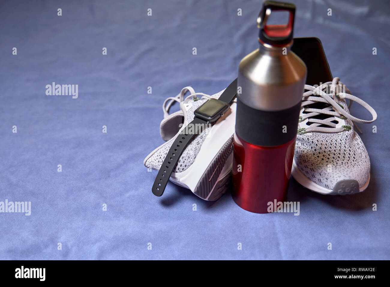 Running shoes with technological accessories and next to a water bottle on a blue towel - Stock Image