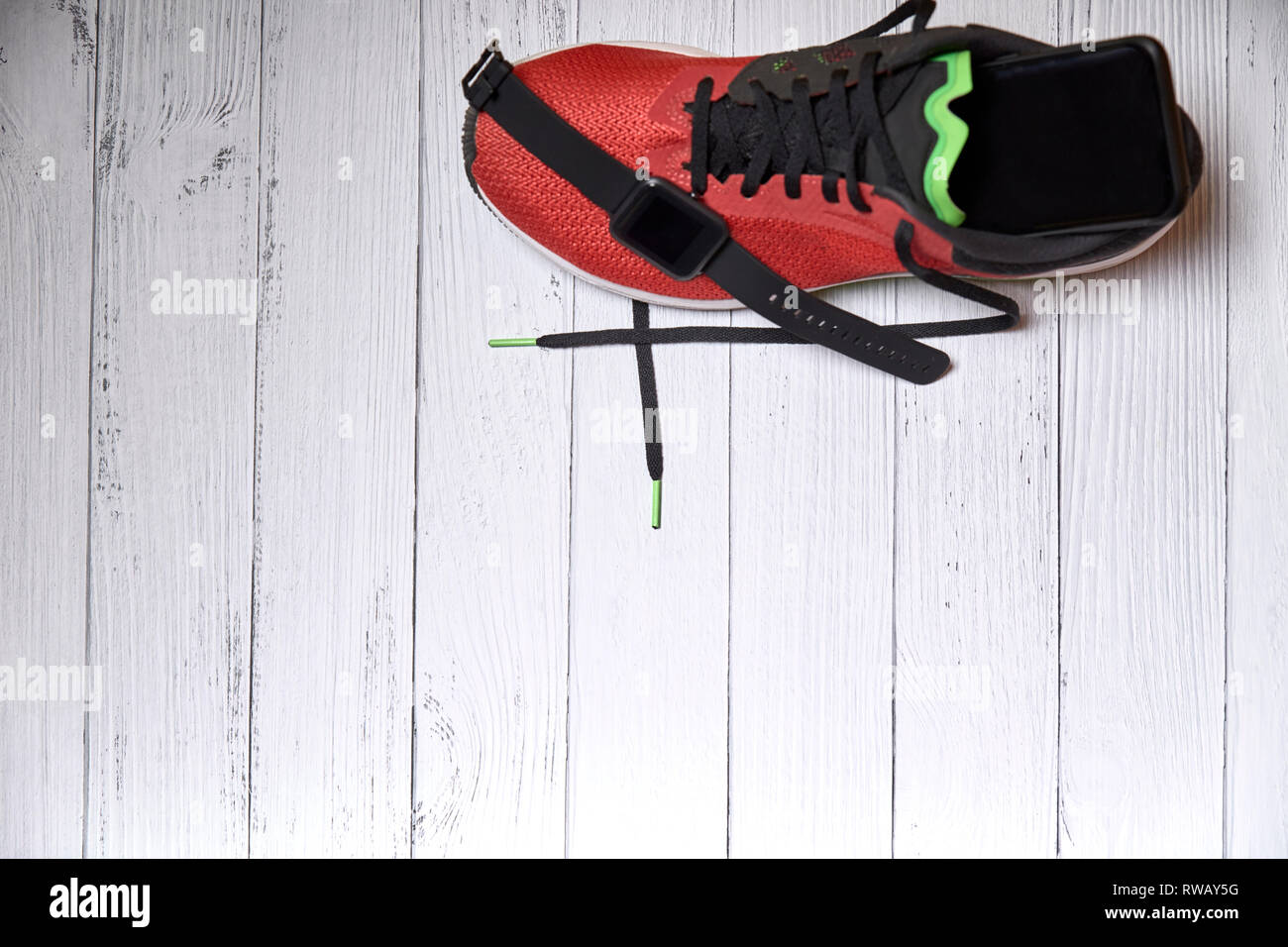 running shoes with technological accessories on white wooden boards - Stock Image