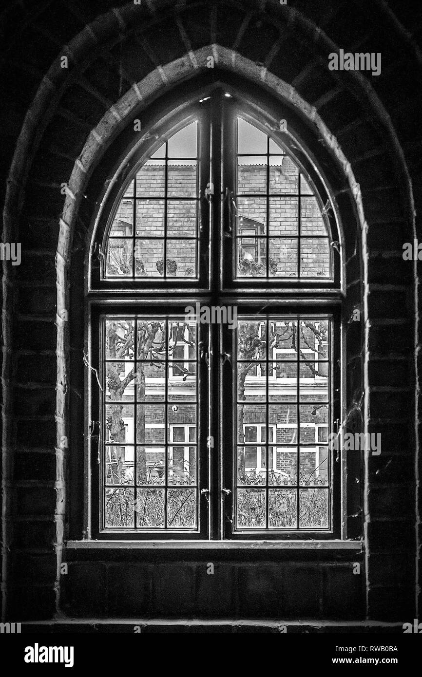 Through the an arched window at the church of Saint Mary in the old town of Helsingor in Denmark. - Stock Image