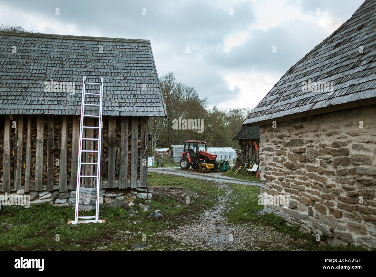 Farm buildings with various agriculture equipment and tractor. - Stock Image
