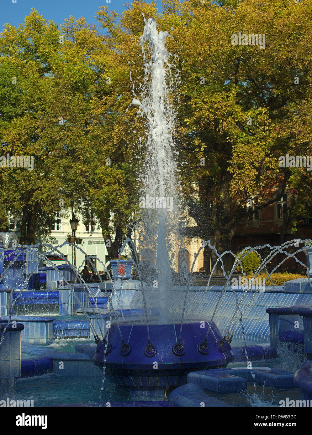 Fountain made of blue marble with water splashing around - Stock Image