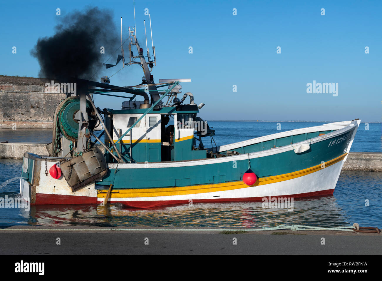 France, Oléron, 2018.  Black diesel fumes exhaust, generated by a small fishing boat as the Captain prepares the trawler to leave the port of  Château - Stock Image