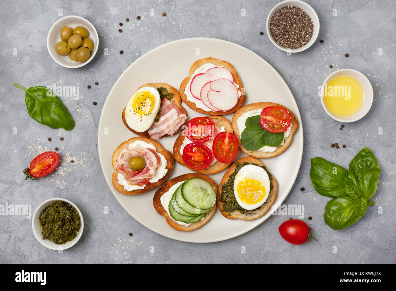 variants of sandwiches with cream cheese, pesto, tomatoes, cucumber, egg, bacon, radishes on a gray background. view from above Stock Photo