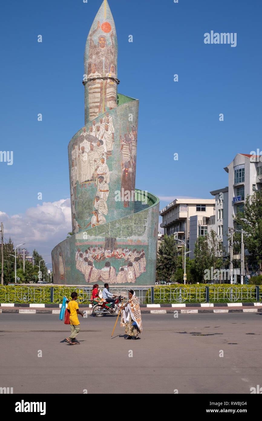 Ethiopians walk past the Sidamo Monument in Hawassa (Awasa) in Ethiopia. It represents the Sidama people's heritage - Stock Image