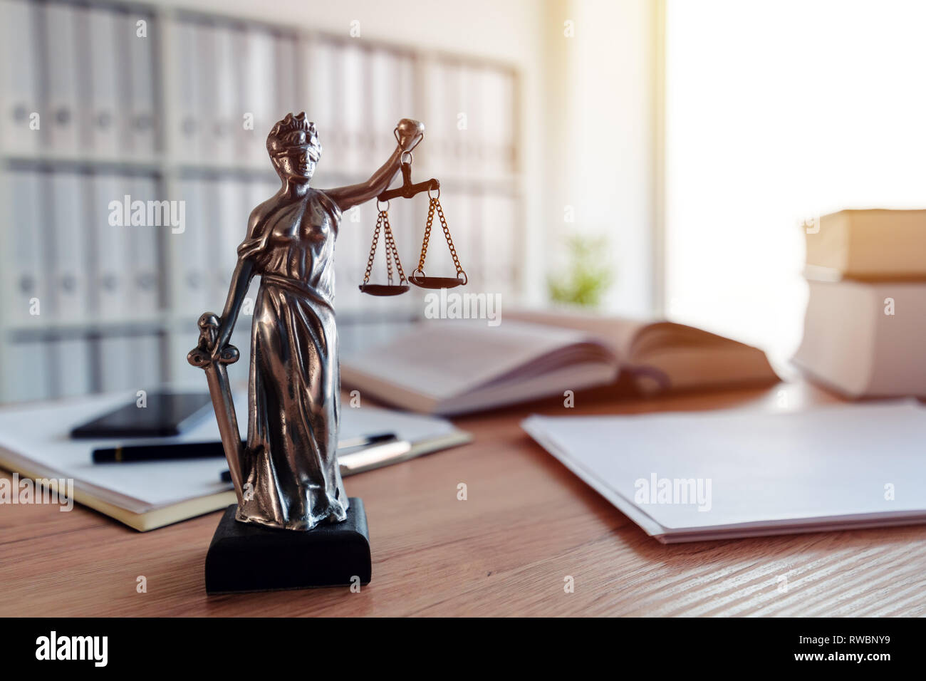Lady Justice statue in law firm attorney office, blindfolded Justitia with balance scales and sword is personification of moral force in judicial syst - Stock Image