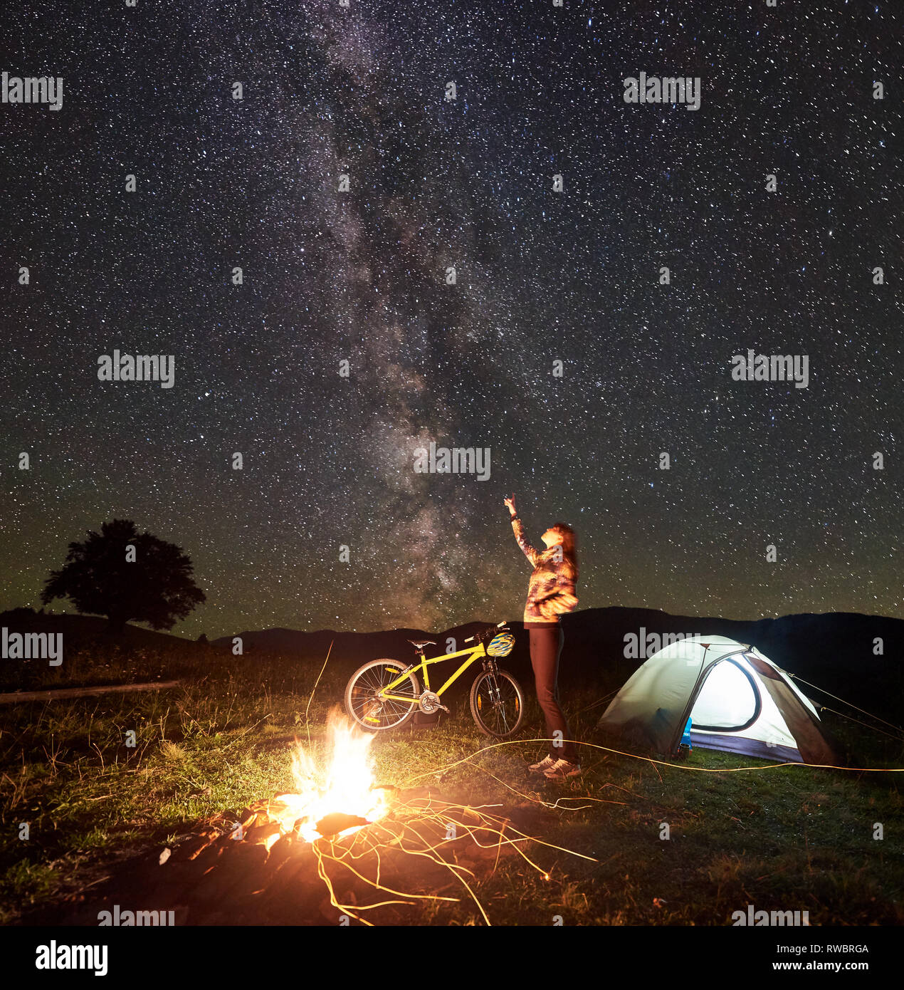 Young woman tourist resting at night camping, pointing at incredible beautiful evening sky full of stars and Milky way, standing near burning campfire, illuminated tent, mountain bike. Tourism concept - Stock Image