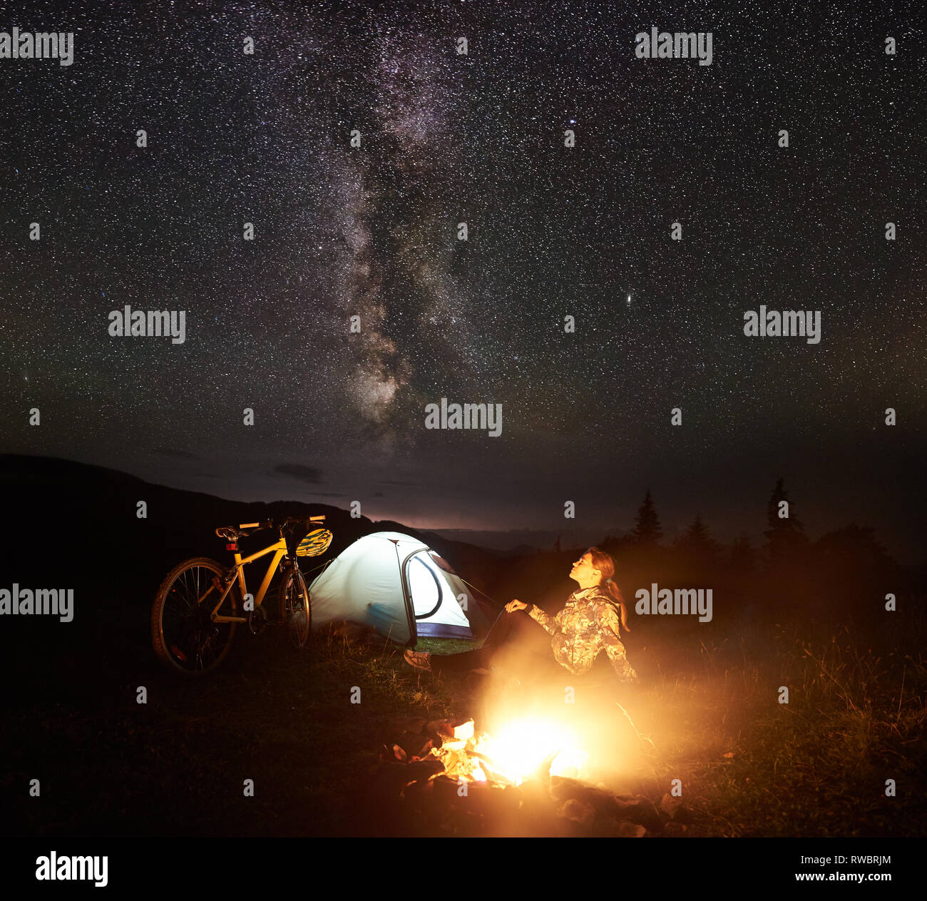 Young woman tourist enjoying at night camping near burning campfire, illuminated tourist tent, mountain bicycle under amazing beautiful evening sky full of stars and Milky way. Astrophotography - Stock Image