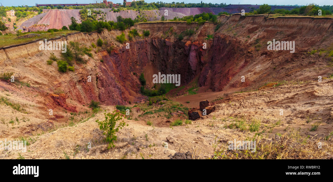 Ground collapsed sinkholes at the daylight. A sand ground breed. Iron ore breed technogenic landscape. Ukraine, Kriviy Rih - Stock Image