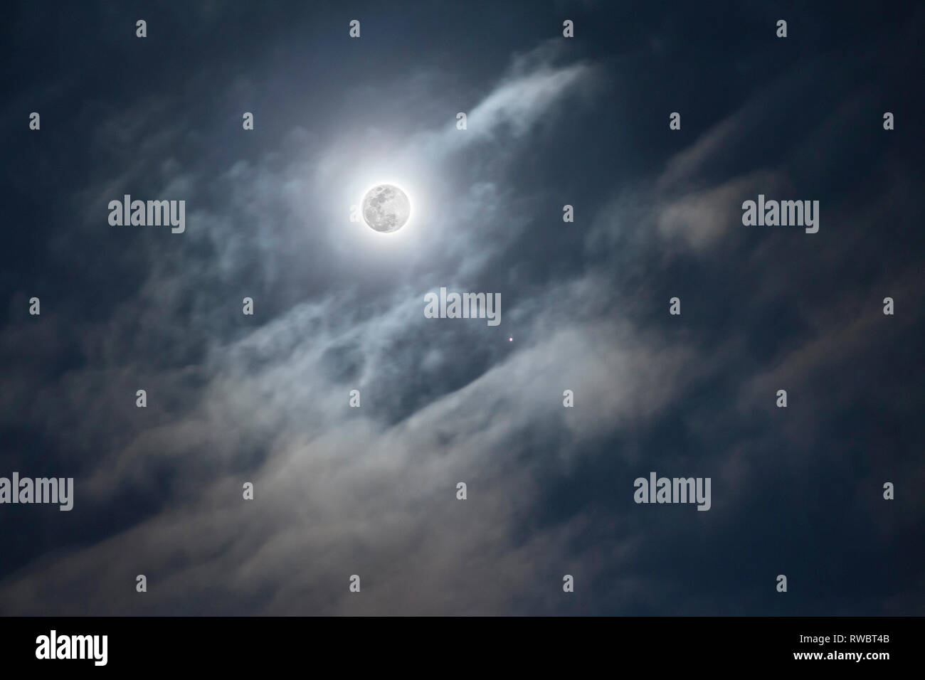 A full Moon on cloudy sky background. Jupiter planet with moons. Telescopic astrophotography. Astronimical event - Stock Image