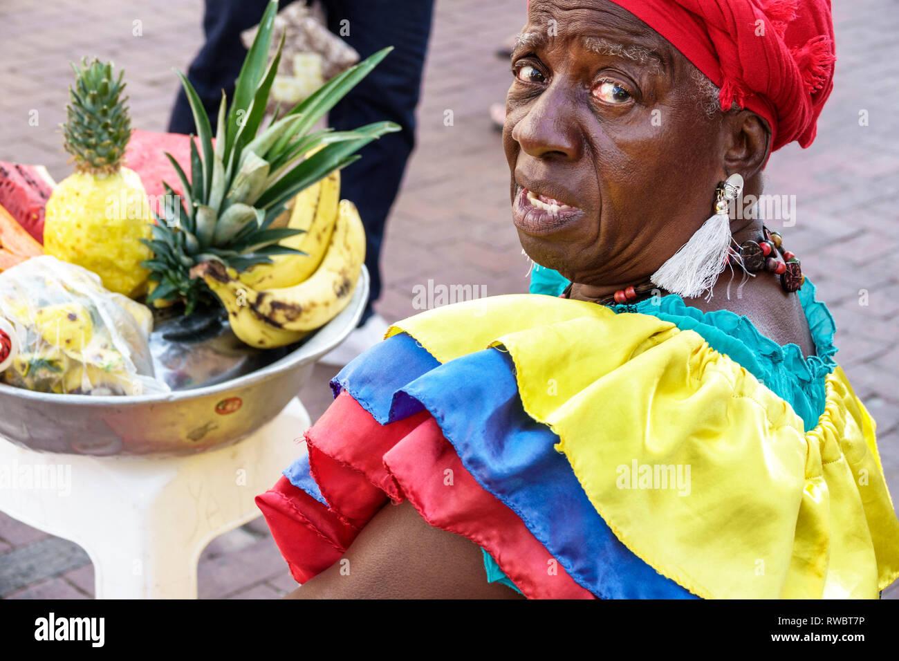 Cartagena Colombia Old Walled City Center centre Centro Plaza San Pedro Claver Black Afro Caribbean Palenquera woman fruit vendor traditional costume - Stock Image