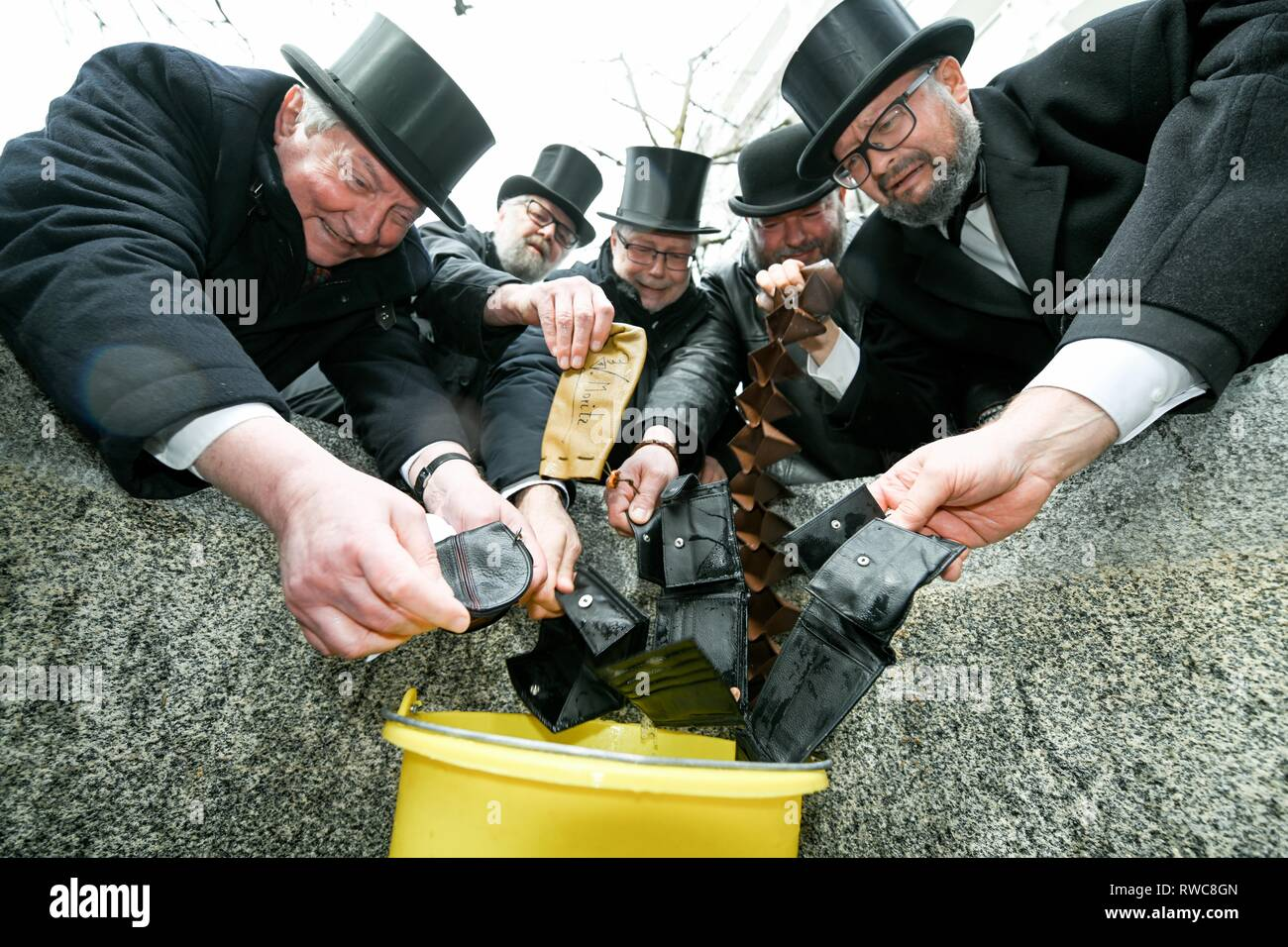 Friedrichshafen, Germany. 06th Mar, 2019. Mourning fools in tail coats and with top hats cry after the traditional purse laundry of the past carnival. Following the customs, the fools wash their wallets on Ash Wednesday in the fountain of the Friedrichshafen district Hofen. Credit: Felix Kästle/dpa/Alamy Live News - Stock Image