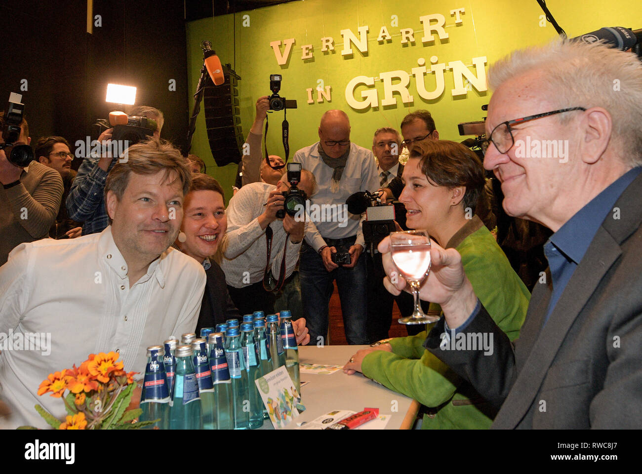 Biberach, Germany. 06th Mar, 2019. Political Ash Wednesday of the Greens in Baden-Württemberg in the Stadthalle. The politicians (l-r) Robert Habeck, federal chairman alliance 90/ the Greens, the two regional chairmen olive Hildenbrand and Sandra Detzer and Winfried Kretschmann, Prime Minister Baden-Wuerttemberg, Greens are surrounded by journalists and drink water. Credit: Stefan Puchner/dpa/Alamy Live News - Stock Image