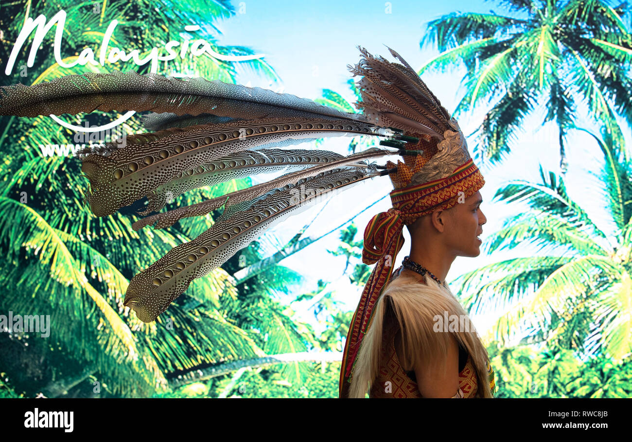 Berlin, Germany. 06th Mar, 2019. A man with a traditional Malaysian headdress stands in front of a photo wall during the opening of the ITB travel fair at the Berlin Exhibition Grounds. Malaysia is the partner country of the 53rd ITB from 06.-10.03.2019. About 10.000 exhibitors from 181 countries and regions present themselves in the exhibition halls at the Funkturm. Credit: Ralf Hirschberger/dpa-zentralbild/dpa/Alamy Live News - Stock Image