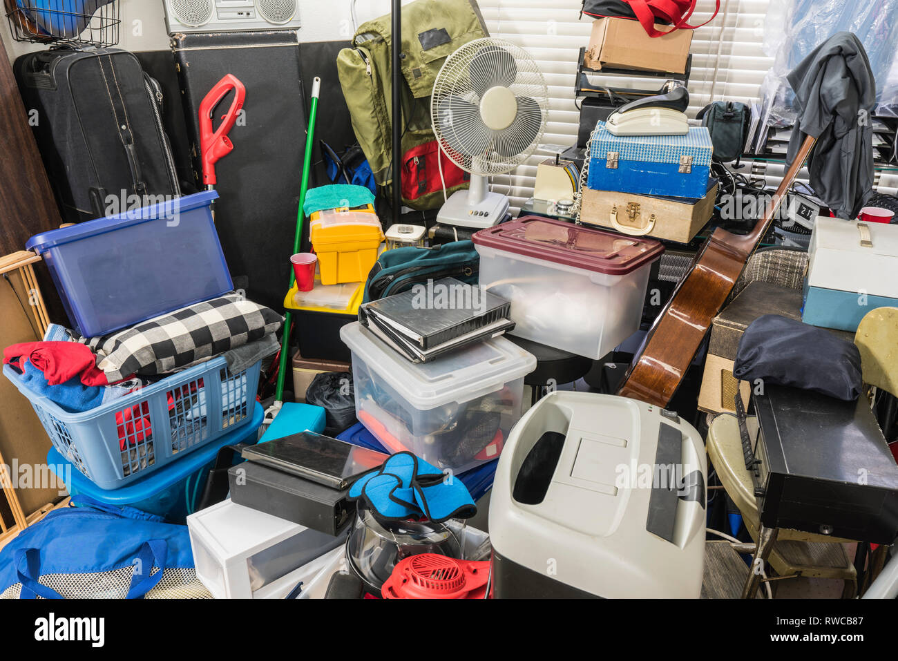 Hoarder home packed with stored boxes, vintage electronics, files, business equipment and household items. - Stock Image