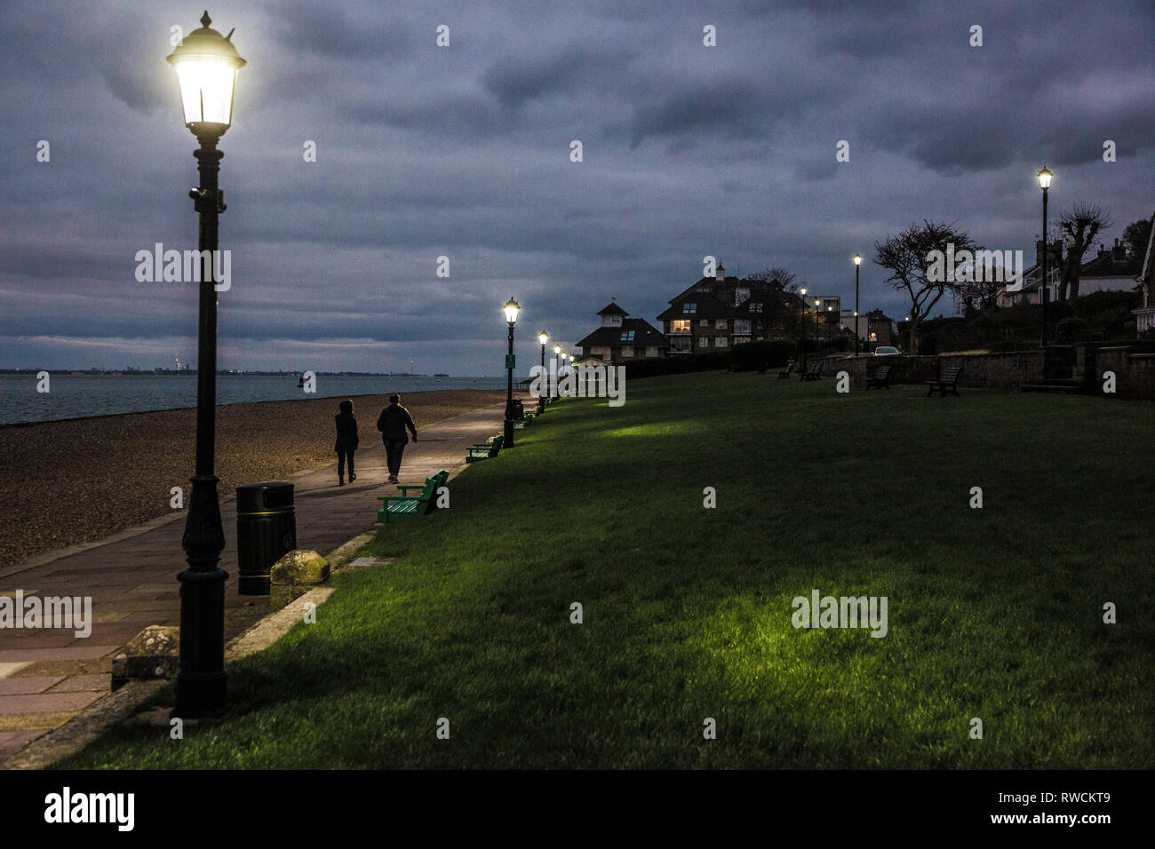 couple walking, along,seafront,the green, at dusk,coast,seafront, parade, street,lighting, new, low,power, LED, lighting, Cowes, Isle of Wight, - Stock Image