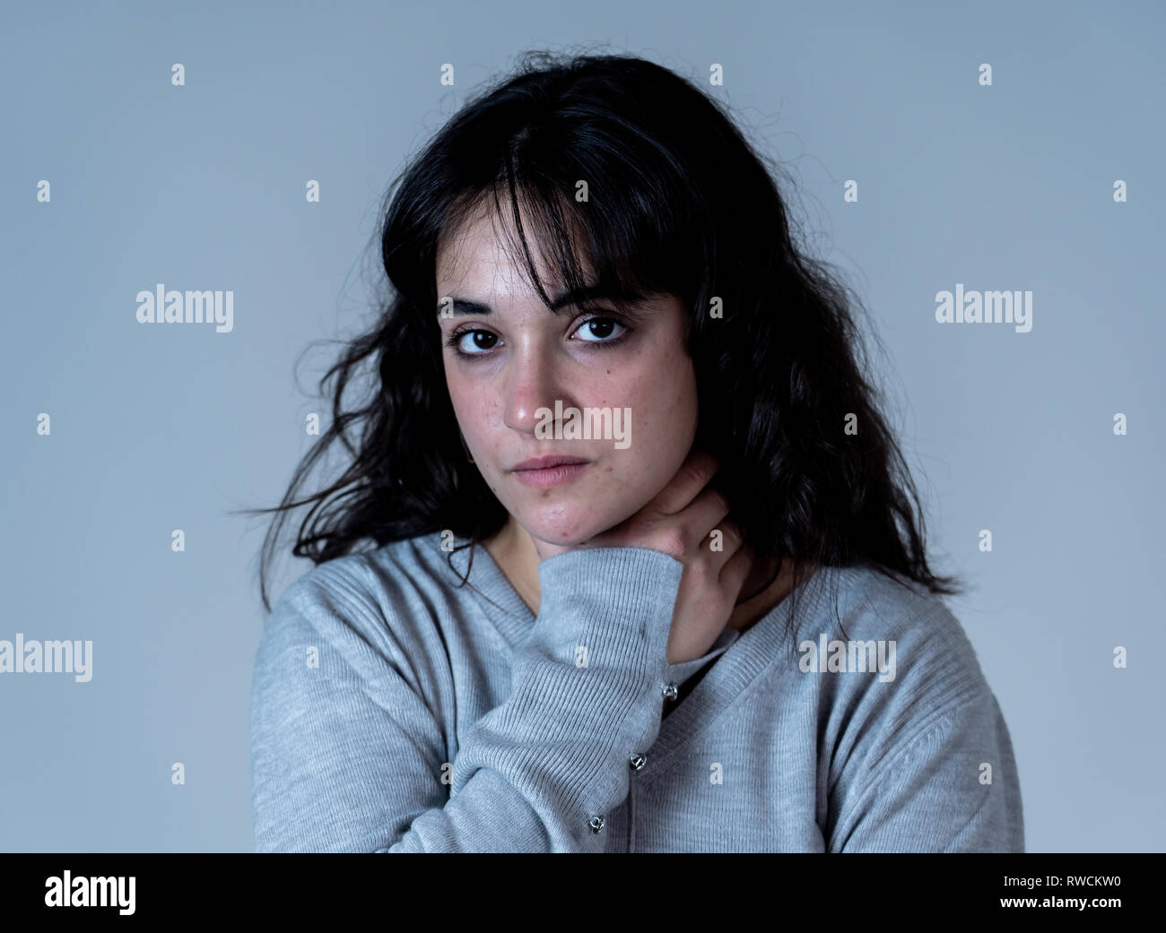 Close up portrait of beautiful young woman with sad eyes looking desperate and melancholy. Human facial expressions and emotions, depression and menta - Stock Image