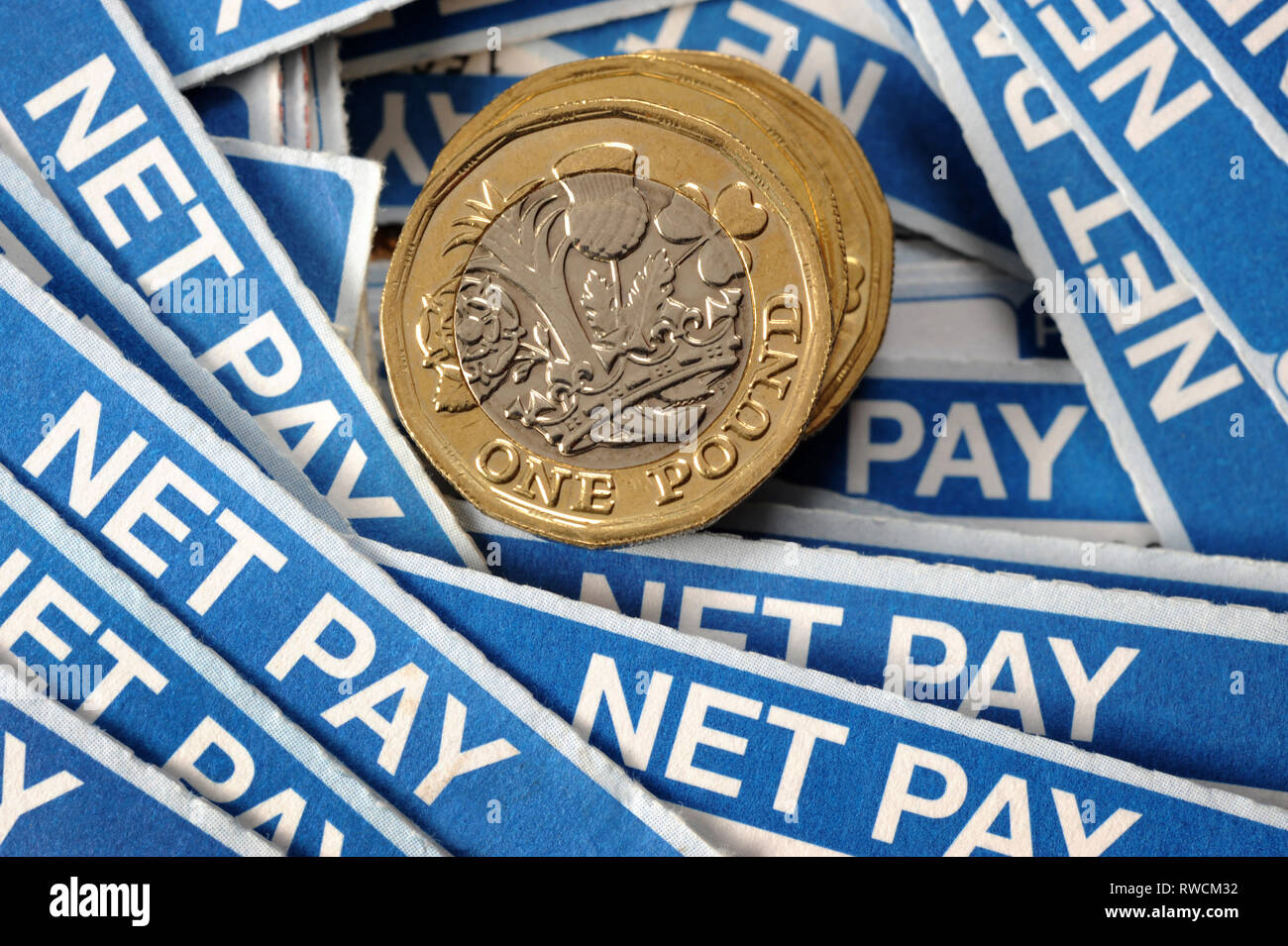 PAYSLIPS WITH ONE POUND COINS RE NET PAY WAGES INCOMES THE ECONOMY MORTGAGES HOUSE BUYERS ETC UK - Stock Image