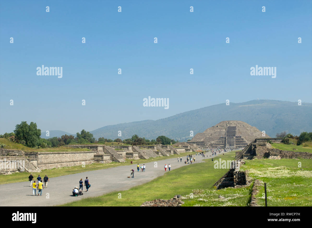 Tourists walking on Avenue of the Dead and the view of Pyramid of the Moon at Teotihuacan, Mexico - Stock Image