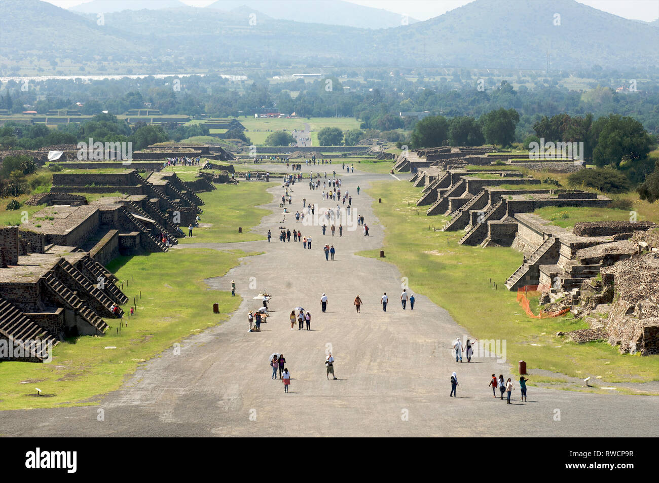 Tourists walking on the Avenue of the Dead at Teotihuacan seen from the pyramid of the Moon in Mexico - Stock Image