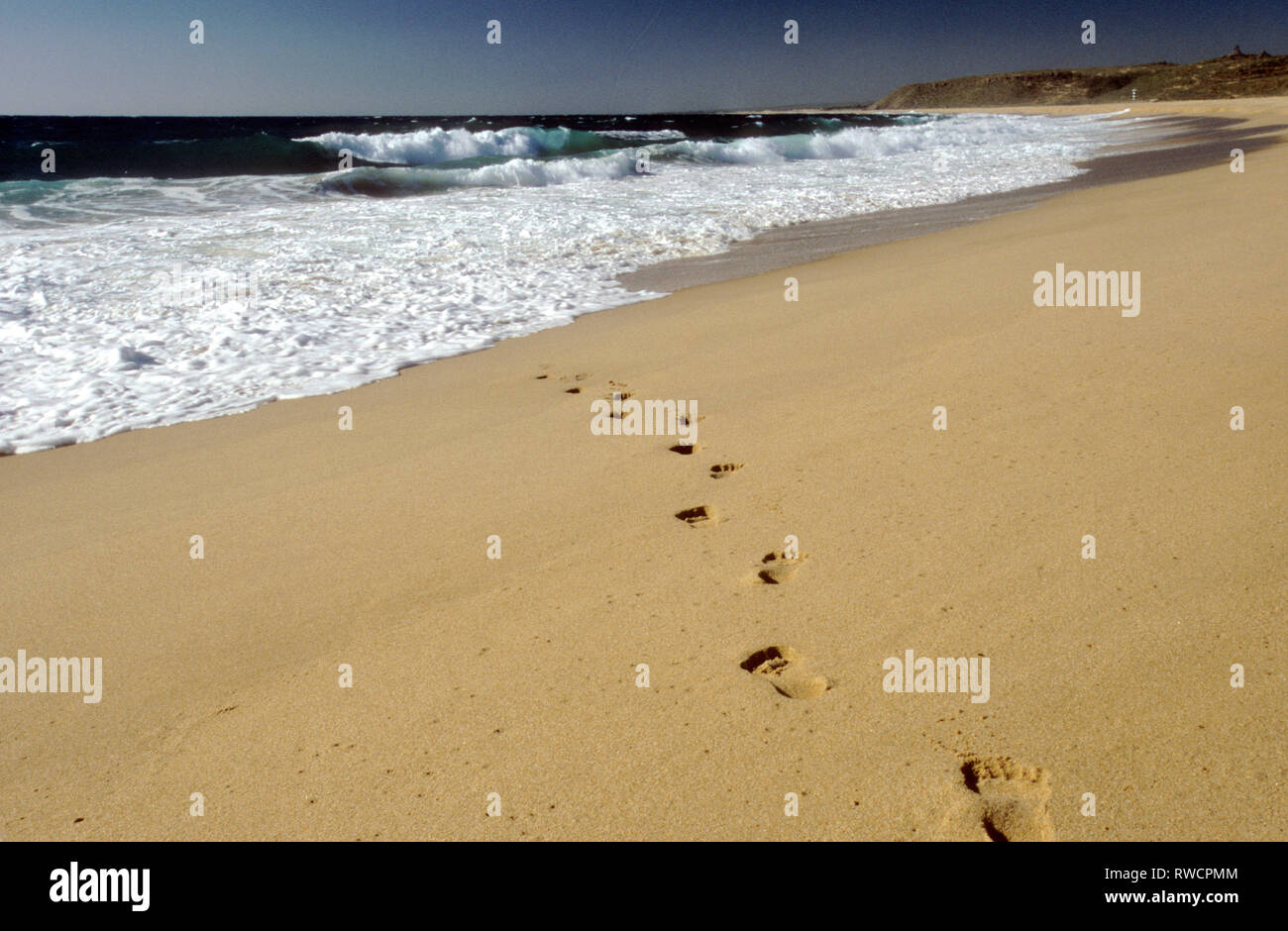 Footprints in the sand vanishing into the surf - Stock Image