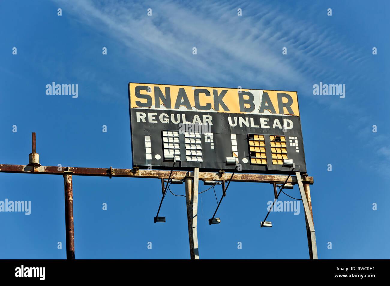Elevated Vintage Gas Station 'Snack Bar - Regular - Unleaded' gasoline,  rusty metal frame, along highway. - Stock Image