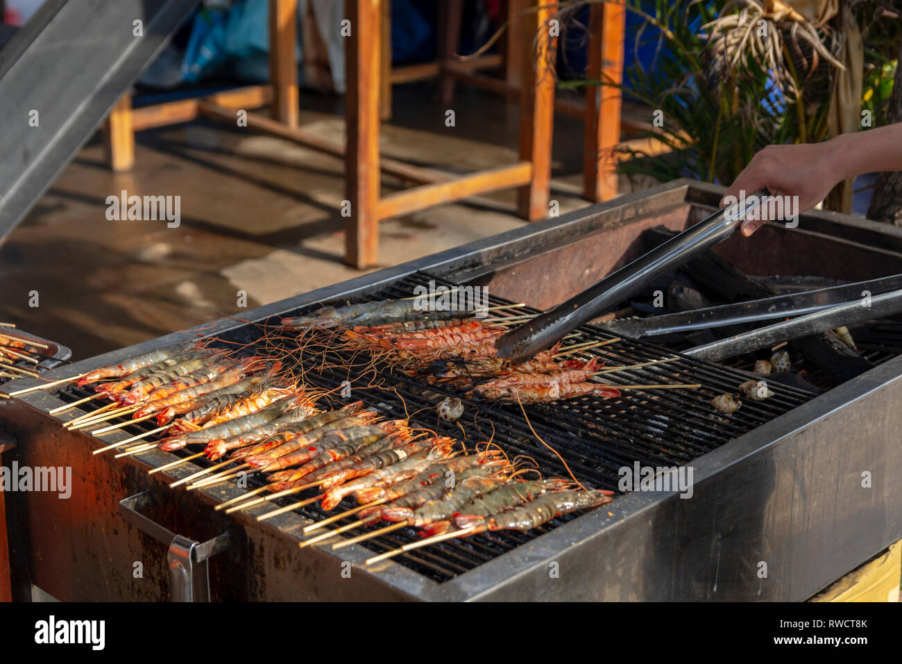 Hand holding a kitchen tong for turning prawns on a coal-fired grill, picture from Phu Quoc Island, Vietnam. - Stock Image