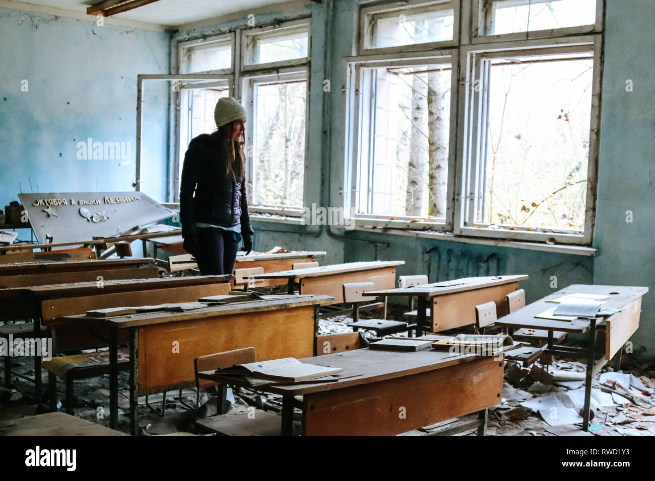 Woman walks through a classroom that was abandoned long ago in wake of the Chernobyl nuclear disaster - Stock Image