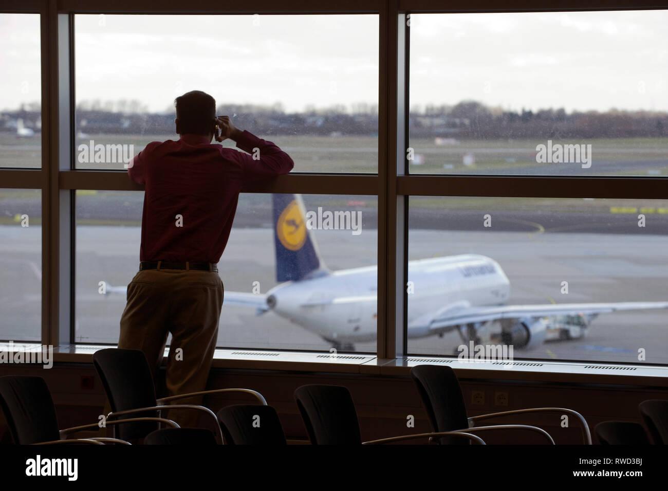 Ein Mann steht in einer Vortragspause am Fenster des Duesseldorfer Flughafen und schaut auf eine Lufthansa Maschine die auf dem Vorfeld parkt. [(c) Di - Stock Image
