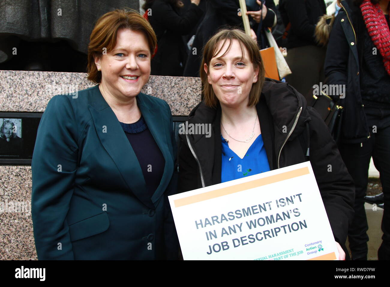Maria Miller [ Conservative ] and Jess Phillips [ Labour ] stand together in Parliament Square, Westminster whilst attending and supporting March 4 women and Muslim women's network UK. on 5th March 2019. Sign being held with the words Harassment isn't in any woman's job description. British politicians. UK politicians. Politics. March 4 Women. - Stock Image