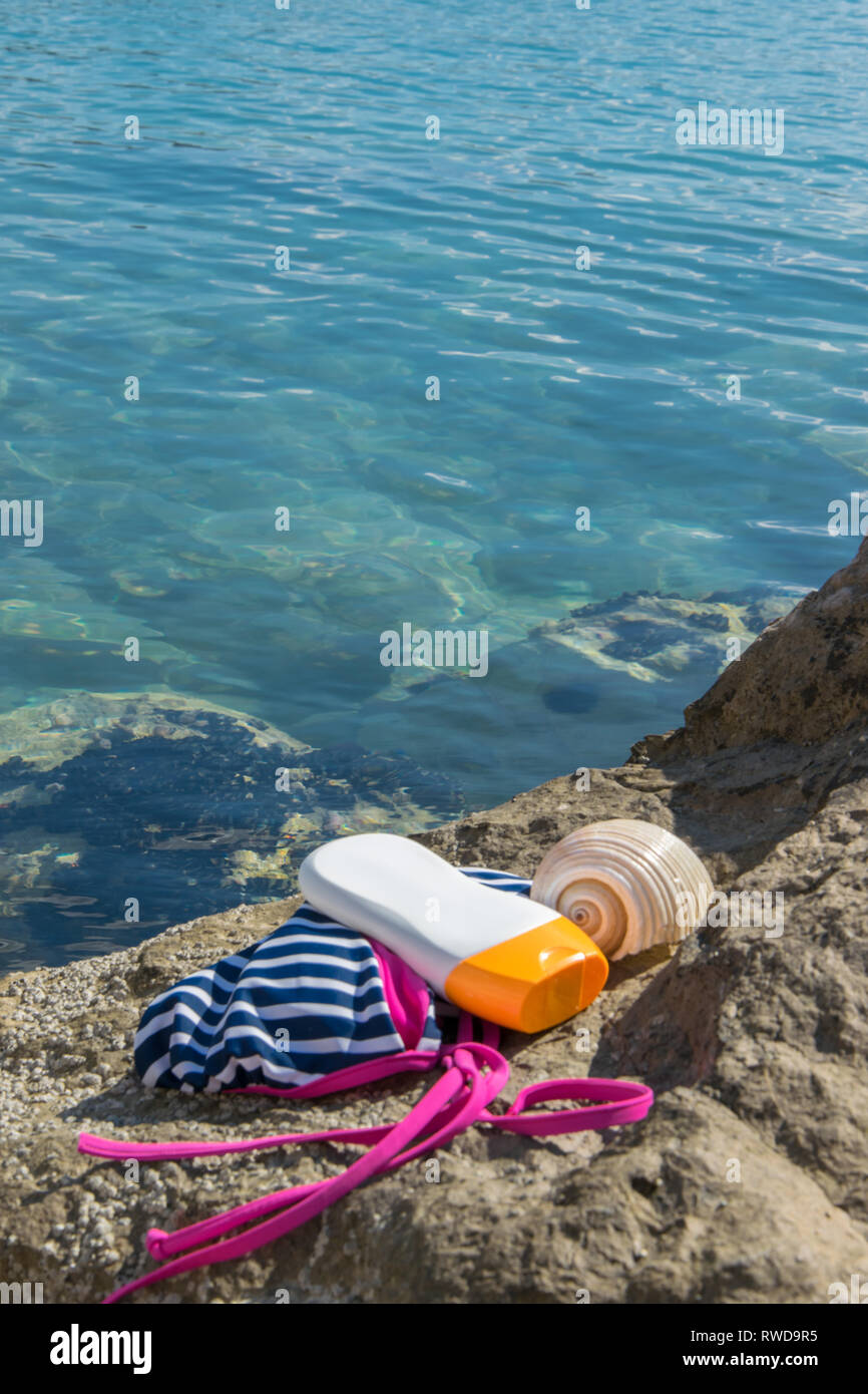 Beach items - swimwear, sun protection cream and a shell on a seashore rock - Stock Image