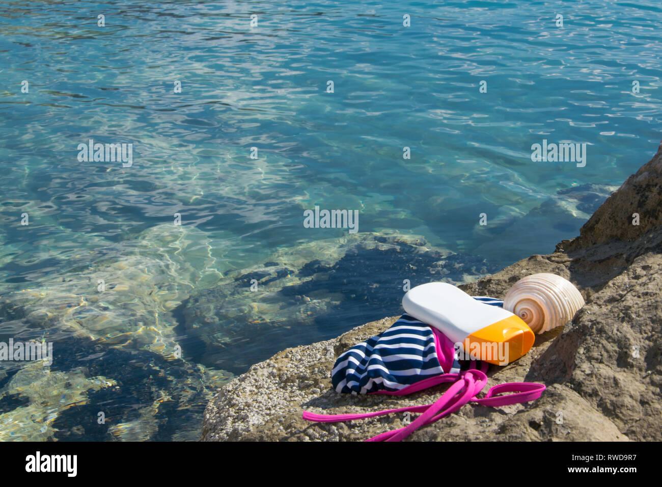Beach items - swimwear, sun protection cream and a shell on a seashore rock - Stock Image