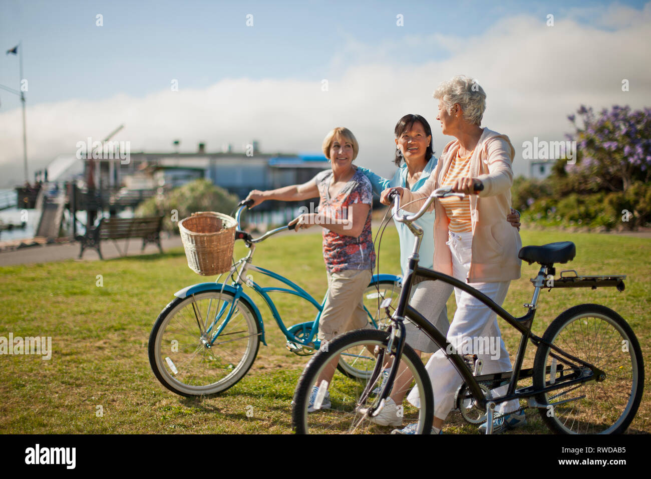 Three mature female friends have fun chatting together as they walk their bicycles through a grassy park. - Stock Image
