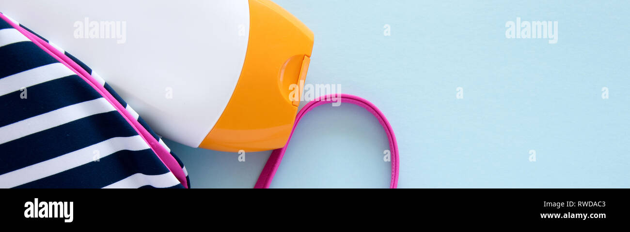 Beach items - swimwear and sun protection cream on light blue background - Stock Image