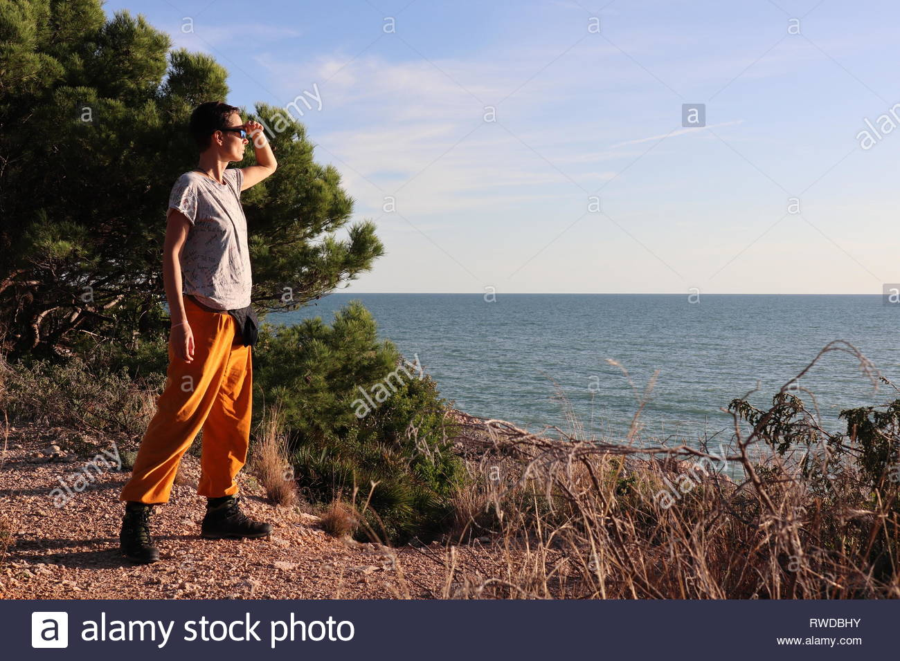 Woman standing at the coast watching the horizon over mediterranean sea - Stock Image
