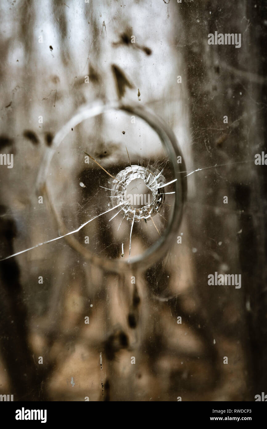 A bullet hole through the window of the kindergarten, created by vandals inside Chernobyl's Exclusion Zone - Stock Image