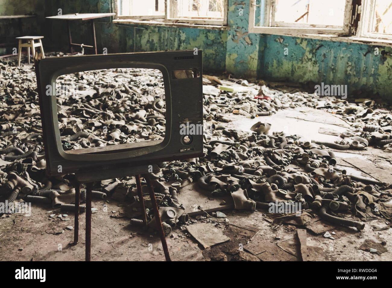 Gas masks that were aquired in case of chemical attack during the cold war now lay on the floor of a classroom inside the Chernobyl exclusion zone. - Stock Image