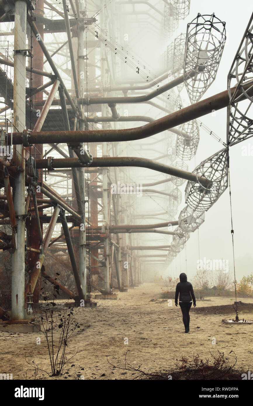 Person explores the abandoned Duga Radar inside Chernobyl's Exclusion Zone - Stock Image