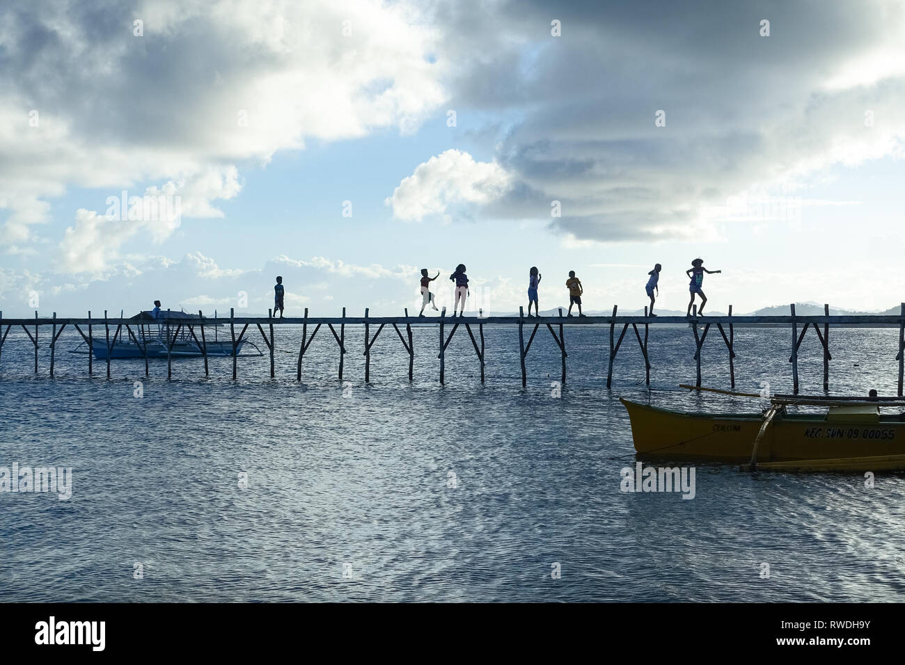 Dancing and Playing Children on Island Pier, General Luna -Siargao, Philippines Stock Photo