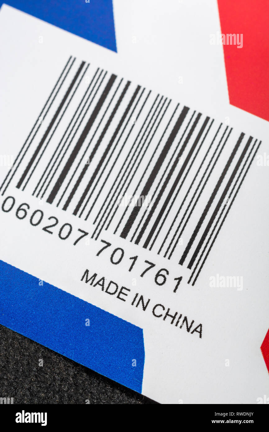 Union Jack flag product stamped with 'Made in China'. Metaphor, cheap Chinese imports, US-China trade war, trade tariffs, China business. - Stock Image