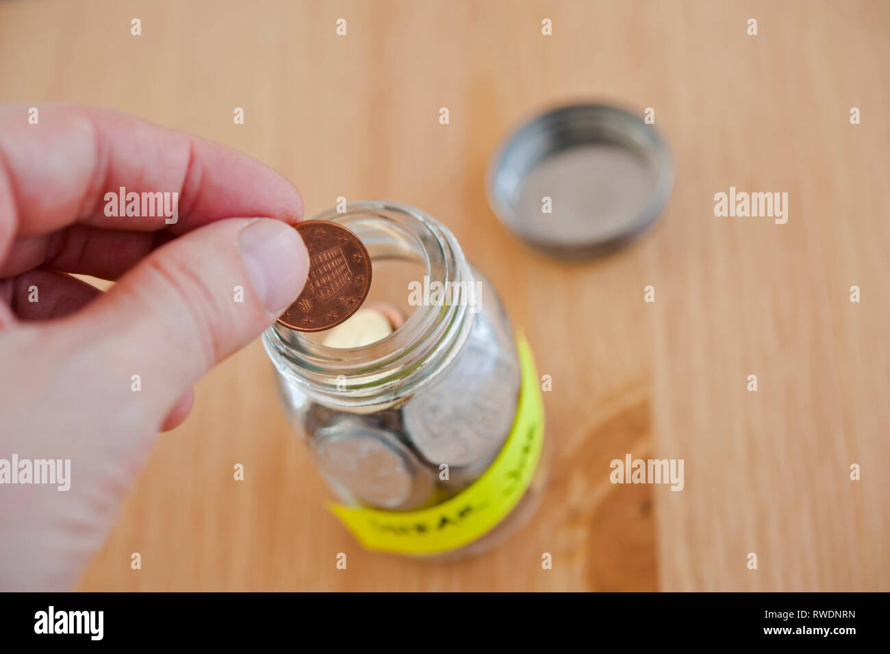 hand putting a coin into a swear jar - Stock Image