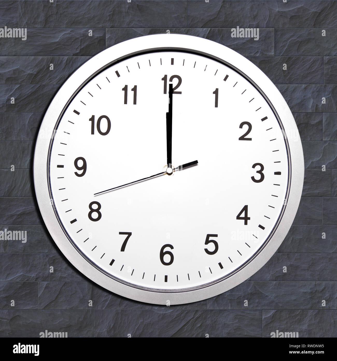 wall clock set at noon or twelve o'clock - Stock Image