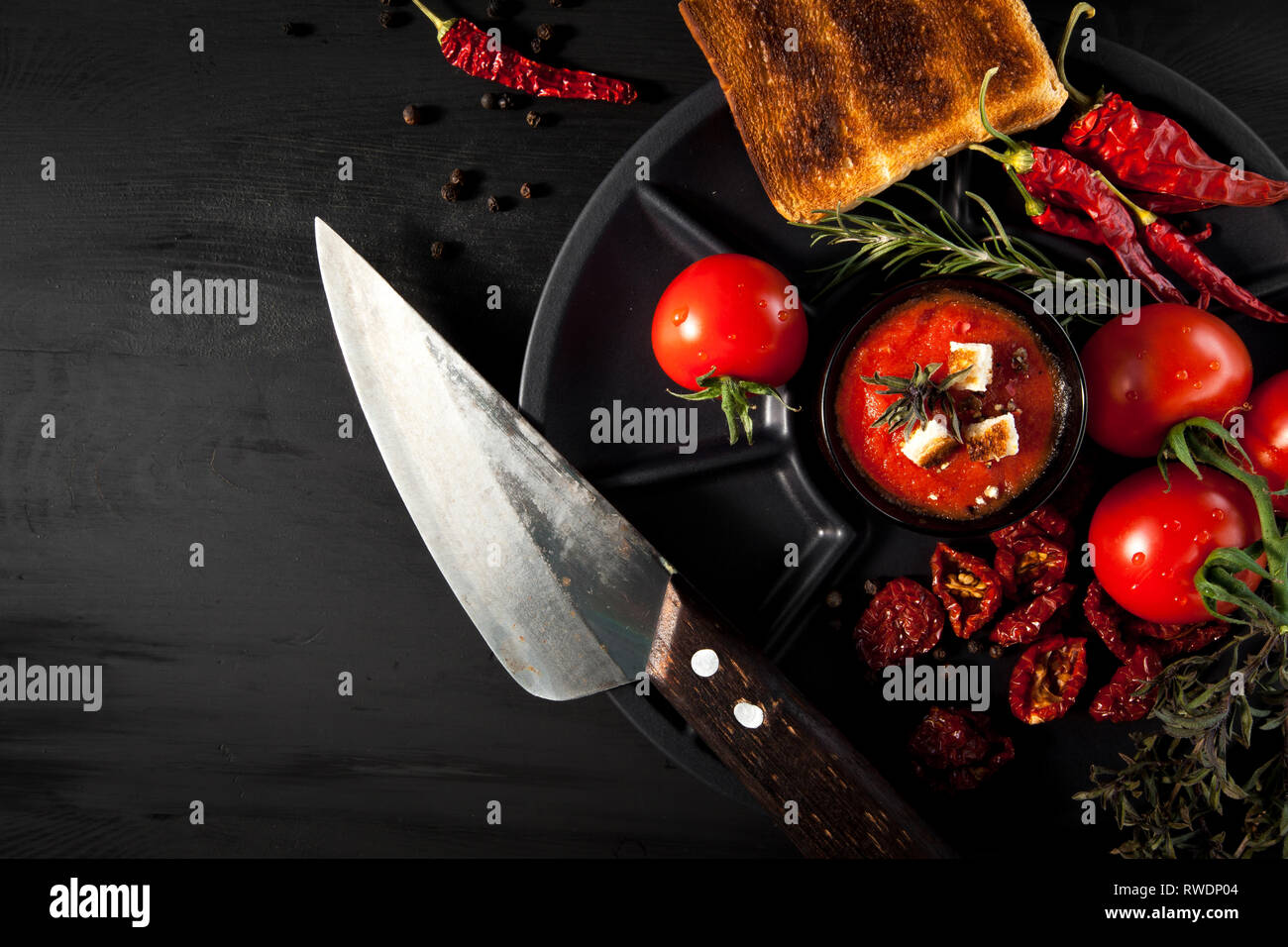 Tomato soup with chili and vegetables. Healthy food. On a black wooden background. Top view. Copy space for your text. Stock Photo