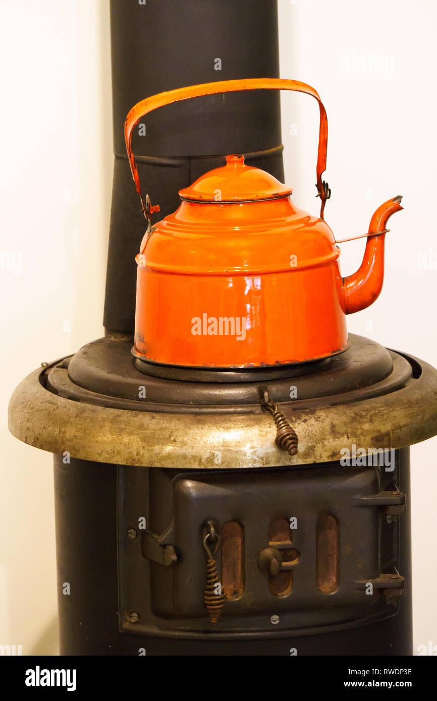 Old stove with orange kettle. Stock Photo