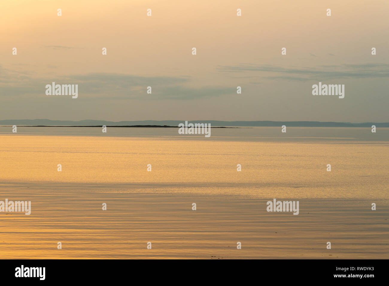 Minimalist landscape showing the evening last sunlight in summer time on the St.Lawrence River, Province of Quebec, Canada - Stock Image
