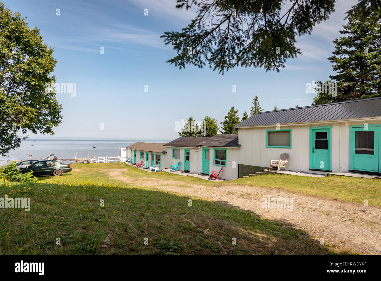 Old but comfy motel painted in white and light blue overlooking the St.Laurence River, Province of Quebec, Canada - Stock Image