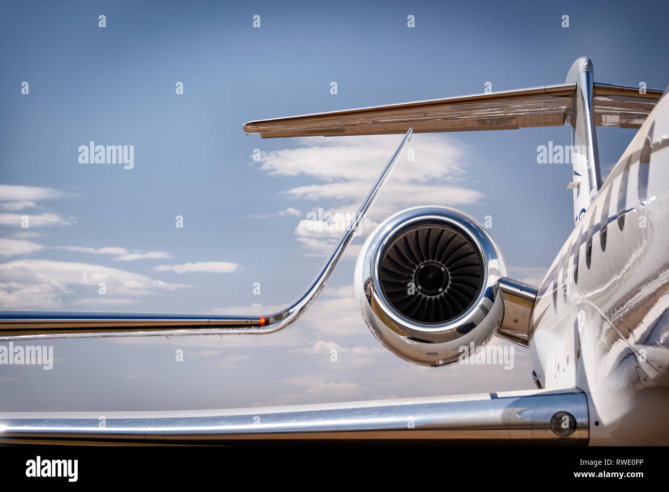 A winglet and engine of a luxury personal jet aircraft against a blue sky with cloud - Stock Image