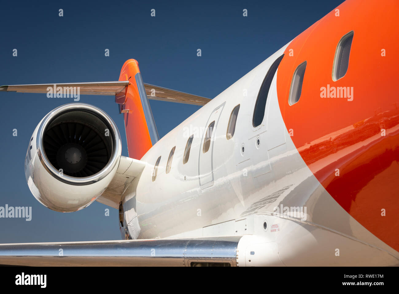 A white and orange private jet airplane against a blue sky - Stock Image