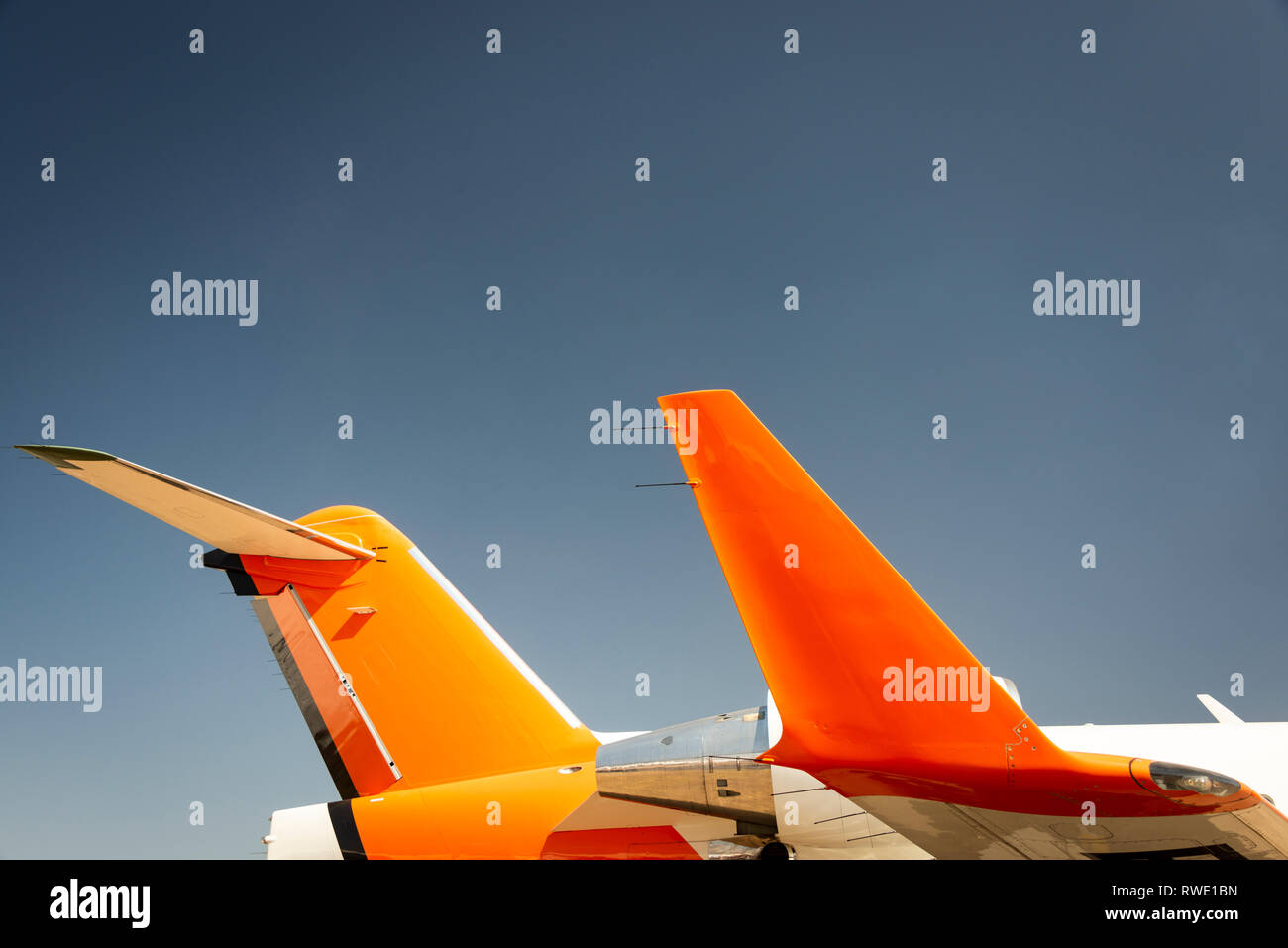Winglet and tail of a jet aircraft, painted orange and white - Stock Image